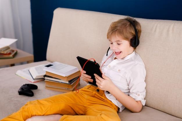 소년 소파에 앉아 팝 옥수수를 먹고 집에서 자신의 온라인 수업 중 격리, 자기 격리, 온라인 교육 개념 동안 사회적 거리 동안 게임 패드와 함께 연주