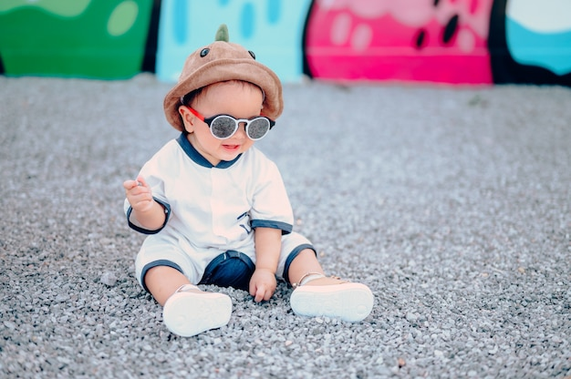 Мальчик сидит на полу на детской площадке