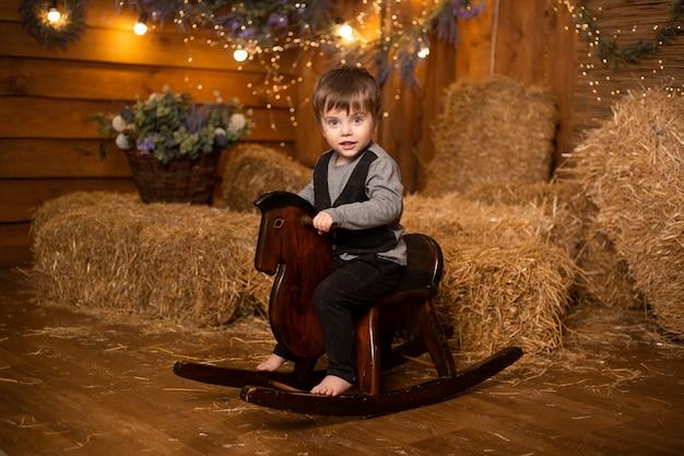 わらの束とファームバックグラウンドでおもちゃの馬に座っている少年