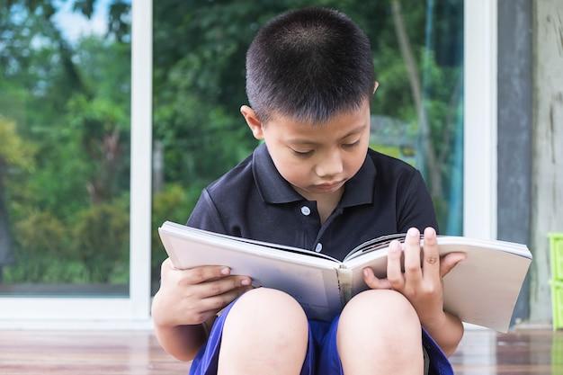 A boy sitting reading a book