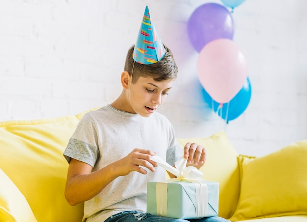 Boy sitting on sofa unwrapping birthday gift