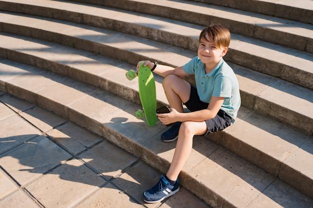 Ragazzo che si siede sulle scale con lo smartphone in mano e penny verde a bordo guardando video divertenti