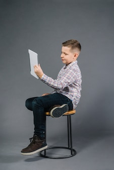 A boy sitting on stool looking at digital tablet against gray background