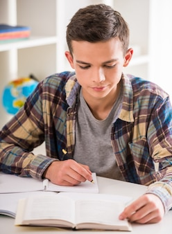 Boy sitting at the table and doing homework at home.