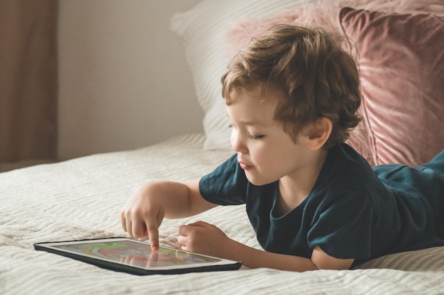 Boy sitting with a tablet on the bed