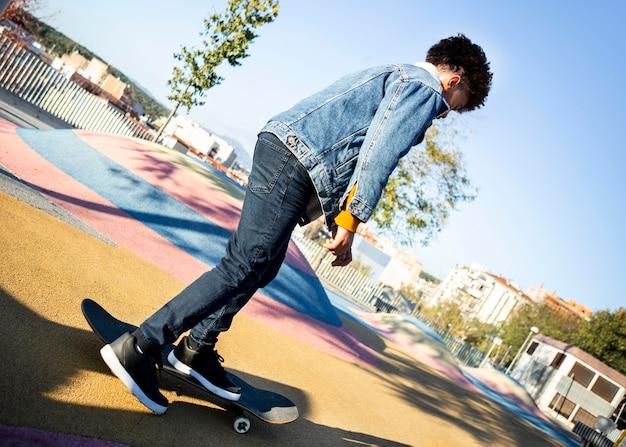 Мальчик катается на скейтборде в парке в одиночестве