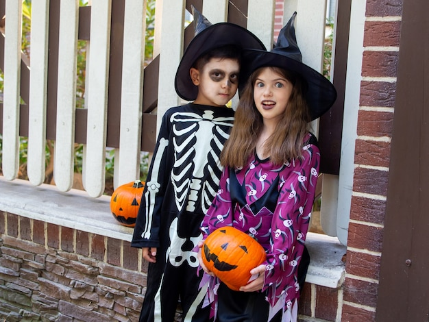 Boy in a skeleton costume and a girl in a witch costume celebrate halloween