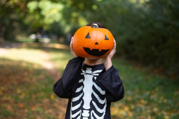 Boy in a skeleton costume with a pumpkin on the holiday of halloween