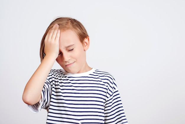 Boy slapping forehead with palm and closing eyes. unhappy kid forgetting something. face emotion and expression. oops, what did i do. back to school and news. oh no. boy thinking about mistakes.