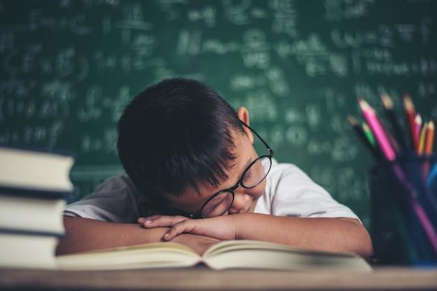 Ragazzo che dorme sui libri in classe.