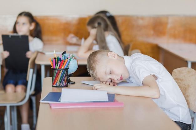 Boy sleeping during lesson in school