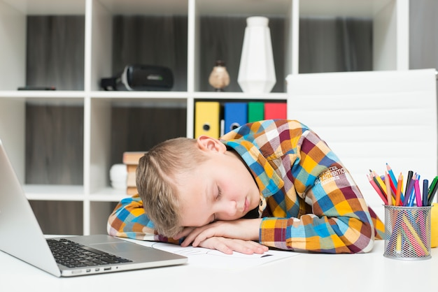 Boy sleeping in front of laptop on desk