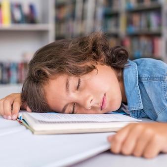 宿題をした後、ノートで寝ている少年