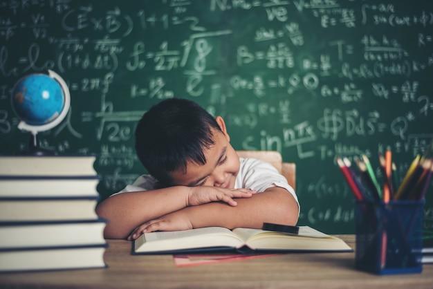 교실에서 책을 자고 소년입니다.