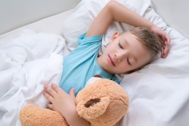 Мальчик спит, сладко обнимая игрушечного медведя