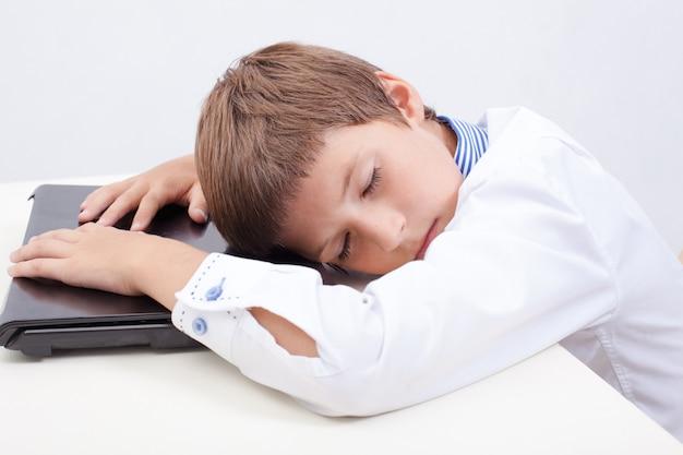 그의 노트북 컴퓨터를 사용하는 동안 자고있는 소년