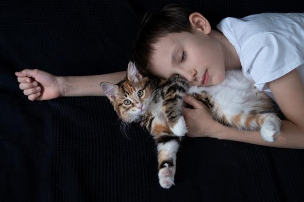 Boy sleeping with small straight kurilian bobtail kitten