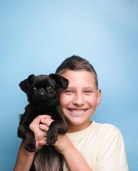 Улыбка мальчика с любимым щенком черной собаки. друзья и счастливая концепция