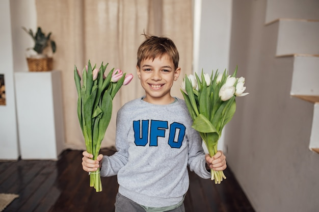 The boy smiles fervently with a bouquet of flowers