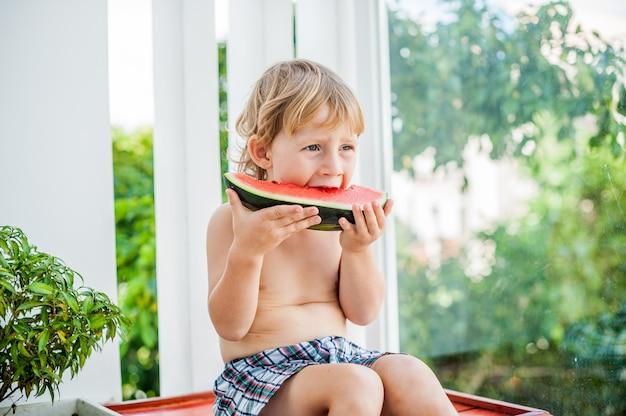 笑顔でスイカを食べる少年