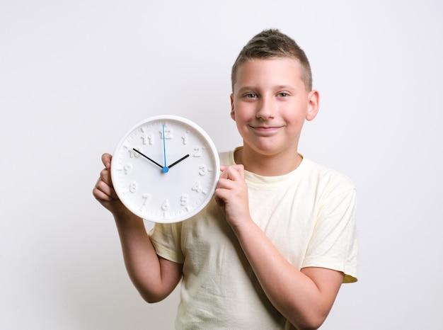 웃으면서 시계 알람 일정과 타이밍 개념을 들고 있는 소년