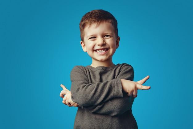 Мальчик улыбается и держит скрещенными руками, показывая жест мира на синей стене