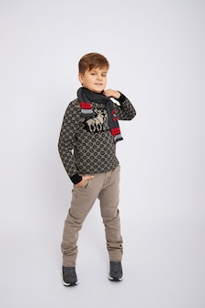 Boy smiling and posing on white background in studio, fashion and clothes.