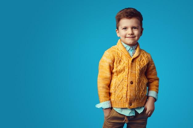 Мальчик улыбается, держась за руки в карманах, изолированных на синем фоне