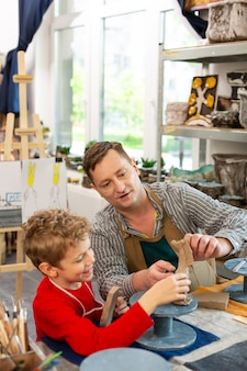 Boy smiling while modeling clay figures with his teacher