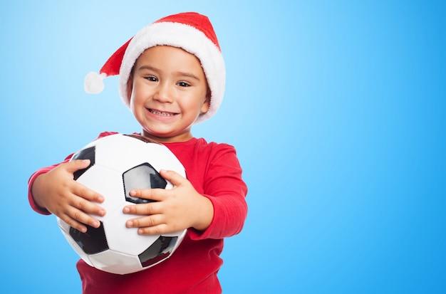 Ragazzo che sorride mentre mostra la sua palla