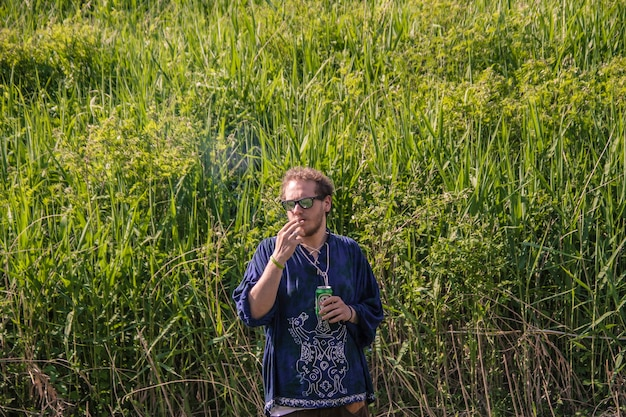 Boy smokes grass and drinks beer immersed in the green of nature