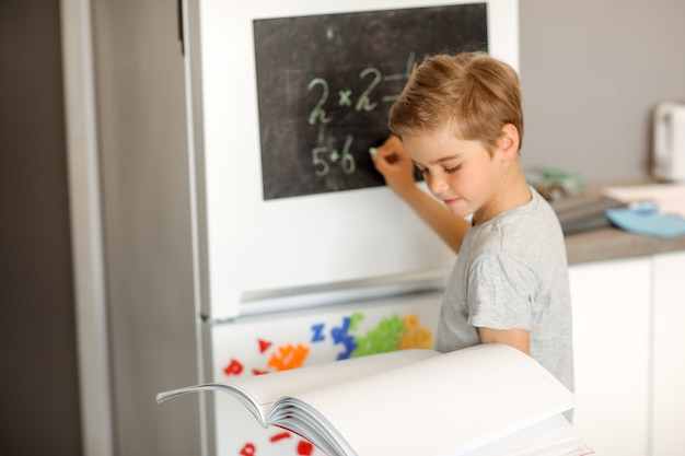 Boy solves math at home on a drawing board