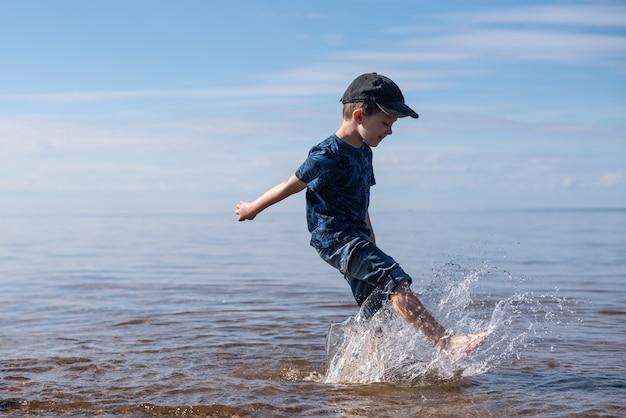 透明な水と青い空を背景に少年がはねかける