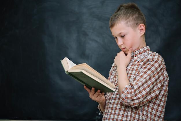 Boy standing against blackboard reading book