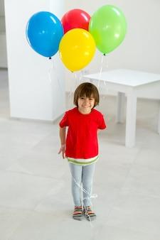 立っていて、風船の束を手に持っている少年