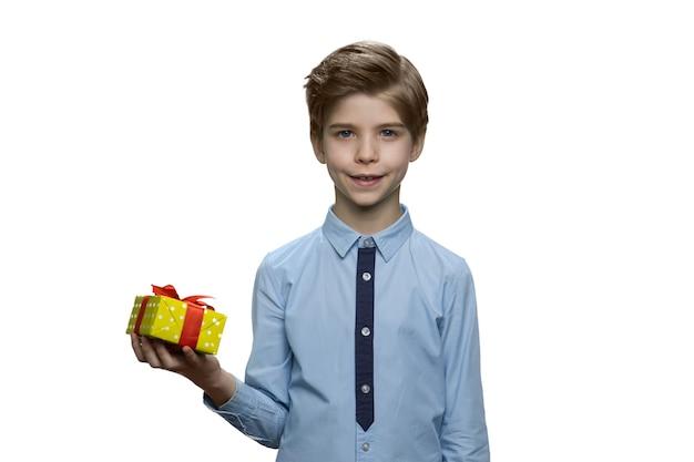 立って小さなギフトボックスを片手に持っている少年