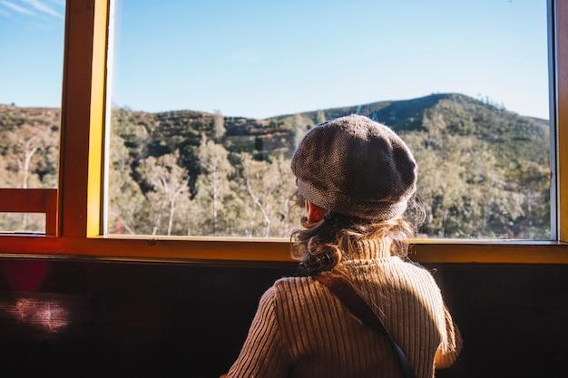 列車の窓に立っている少年