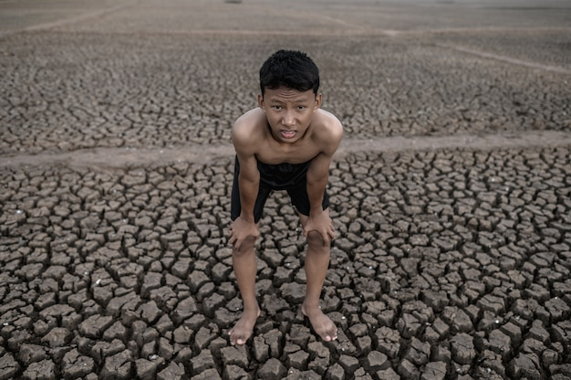 The boy standing bent over and hand catch knees, global warming and water crisis