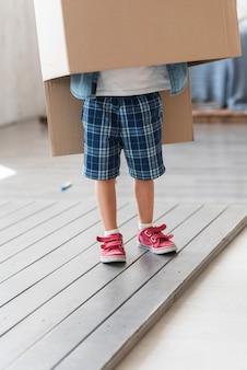 Boy standing under the cardboard box on plank floor