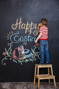 Boy standing and drawing easter doodles on chalk black board