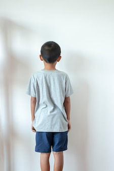 Boy standing in front of the wall in the corner of the roombecause of being punished by parents.