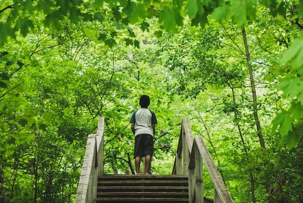 녹색 정글에 서있는 소년 주위에 나뭇잎