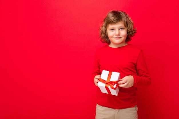 빨간색을 입고 빨간색 배경 벽 위에 고립 된 서 소년