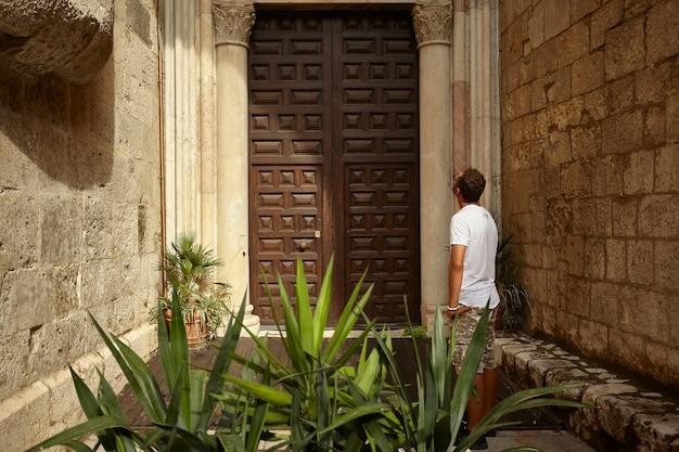 Boy standing looking upwards in front of a door of a historic building.