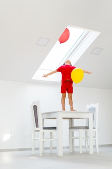 Boy standing on a table while holding a balloon
