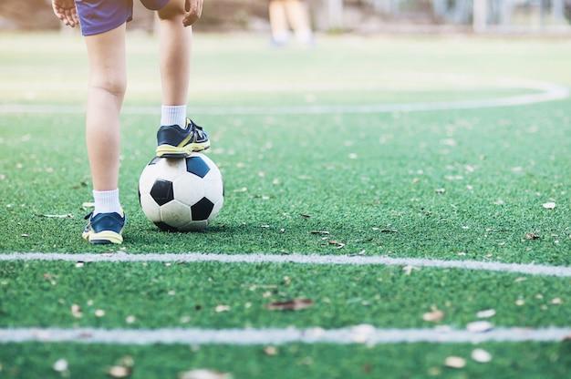 축구장에서 공을 서거나 새로운 게임을 시작할 준비가 된 소년