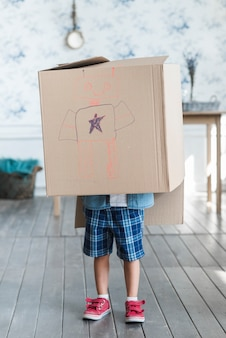 A boy standing with a cardboard box on his head with drawn robot