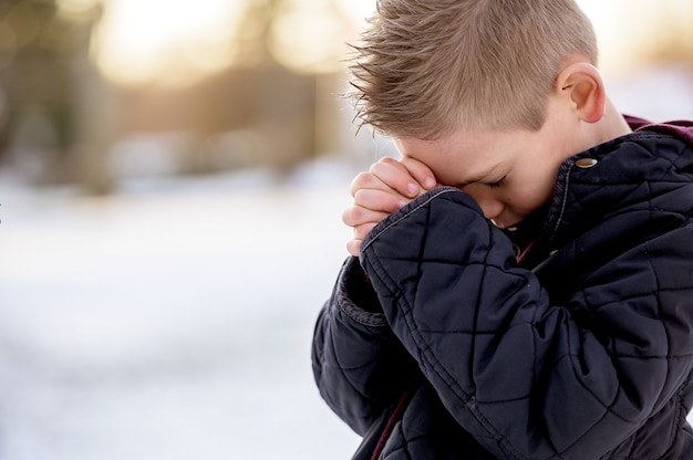 目を閉じて立って祈っている少年