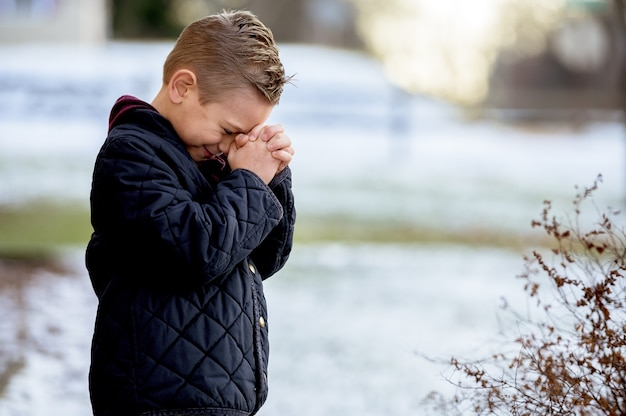 Boy standing with closed eyes and praying
