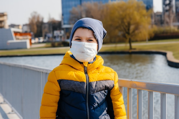 A boy stands on a gray background in a mask during a quarantine with free space. quarantine in the mask